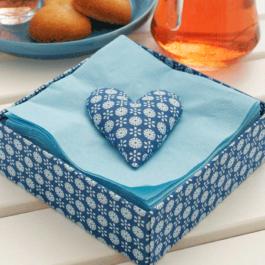 Ett blått servettställ med mönster. Det står på ett vitt dukat fikabord. I servettstället finns det blåa servetter och på servetterna ligger ett hjärta i samma mönster som servettstället för att servetterna inte ska blåsa bort.