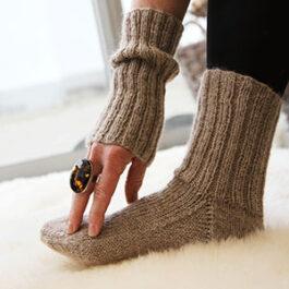 Någons fot med en stickad beige-aktig strumpa och personens arm som nuddar tårna och har matchande stickad pulsvärmare