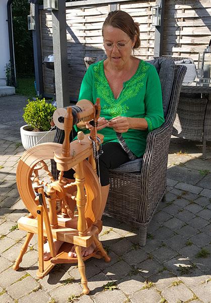 En solig sommardag sitter Helene Sofie ute och spinner.