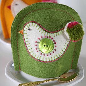 Produktbild: Grön handsydd äggvärmare med en höna som motiv på. Används till påsk