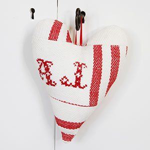 Ett litet uppstoppat vitt hjärta med röda broderier i, som hänger på nyckeln till ett vitt skåp