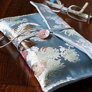 Produktbild: Handsytt bokfodral i blått tyg och löv-mönster på står på ett bord. Det finns en antydan om att det ligger en bok i bokfodralet, men vi kan inte se den så det är stängt. Bredvid ligger ett par läsglasögon.