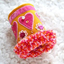 Produktbild: Handsytt armband i gult tyg med rosa hjärtan och paljetter på.
