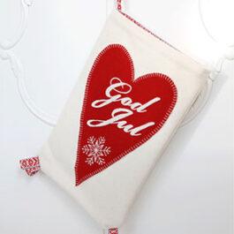 Produktbild: En vit handsydd Julkortsficka med ett hjärta på. På hjärtat är God Jul broderat och även en vit snöflinga