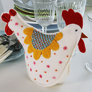 Produktbild: En handsydd påskhöna med broderi på. Används som dekoration till påsken.