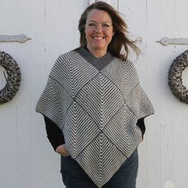 Produktbild: En kvinna som har på sig en grå, stickad poncho med rutiga mönster