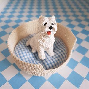 Produktbild: Vit virkad hundkorg med en söt liten prydnadshund i. Används till dockhus