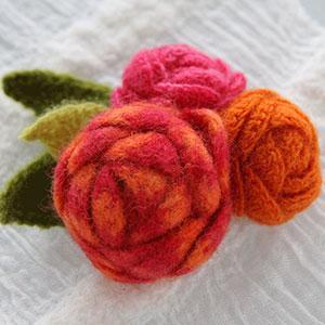 Virkad brosch. Tre virkade rosor i färgerna rosa och orange.