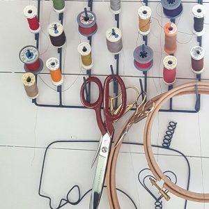 På en vit vägg hänger ett ställ för olika sy tillbehör. På hållaren hänger sytrådar i många olika färger och några saxar.